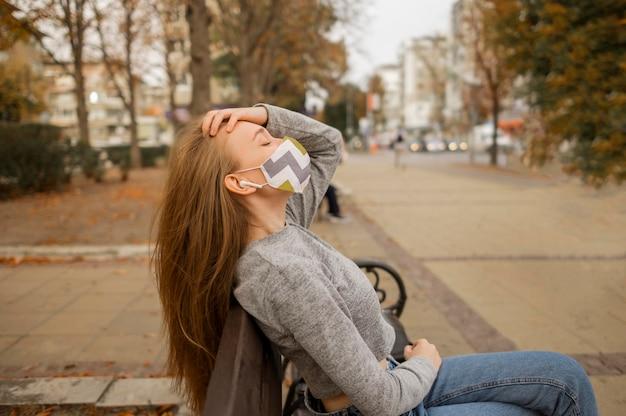 Боком женщина с медицинской маской, сидя на скамейке
