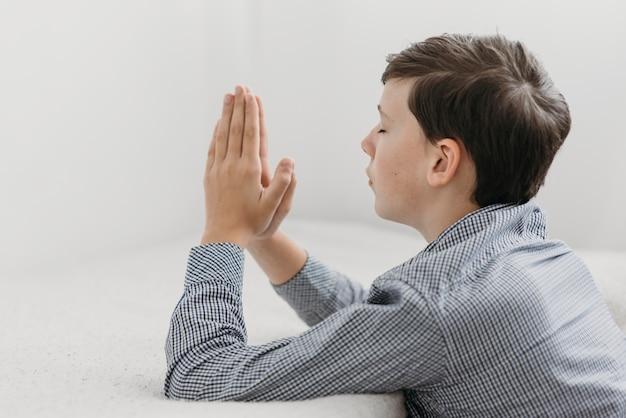Ragazzo di lato giovane che prega pacificamente