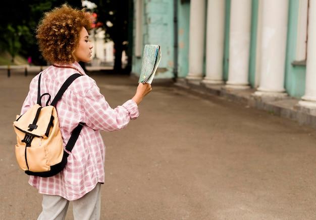 Молодая женщина сбоку проверяет свою карту с копией пространства