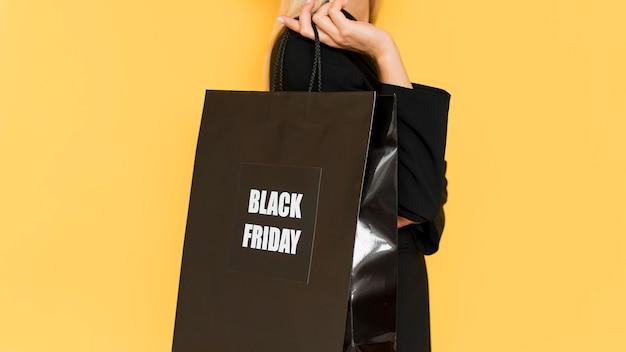 ブラックフライデーの黒のショッピングを保持しているシドウェイ女性