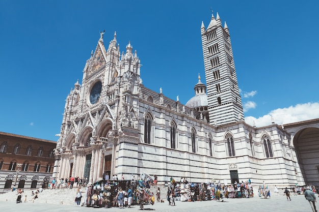 Siena, italy - june 28, 2018: panoramic view of exterior of siena cathedral (duomo di siena) is a medieval church in siena, dedicated from its earliest days as a roman catholic marian church