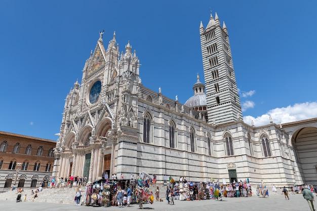 Сиена, италия - 28 июня 2018: панорамный вид снаружи сиенского собора (дуомо ди сиена) - средневековая церковь в сиене, посвященная с самых первых дней ее существования как римско-католическая церковь марии