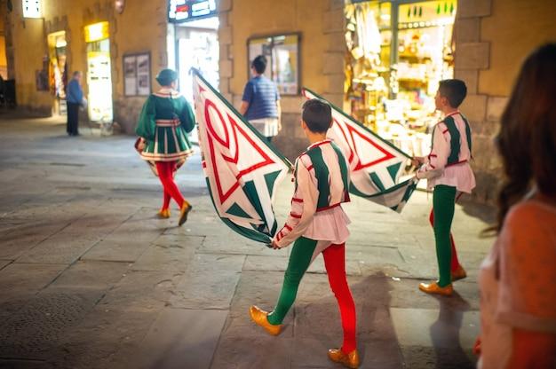 イタリア、シエナ-2018年10月13日:旗を持った地元の人々がシエナの中心部の通りを歩きます