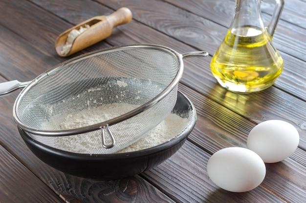 Процедить по черной миске с мукой. стеклянная бутылка с маслом, яйцами, деревянной ложкой с мукой. закрыть вверх