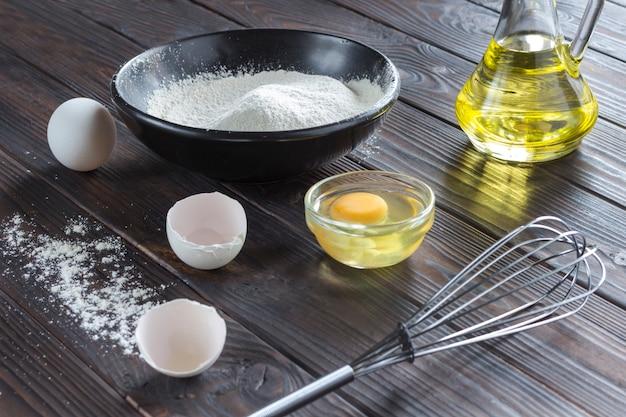 Процедить по черной миске с мукой. стеклянная бутылка с маслом, яйца, яичная скорлупа, разбитое яйцо в тарелке, металлический венчик, деревянная ложка с мукой.
