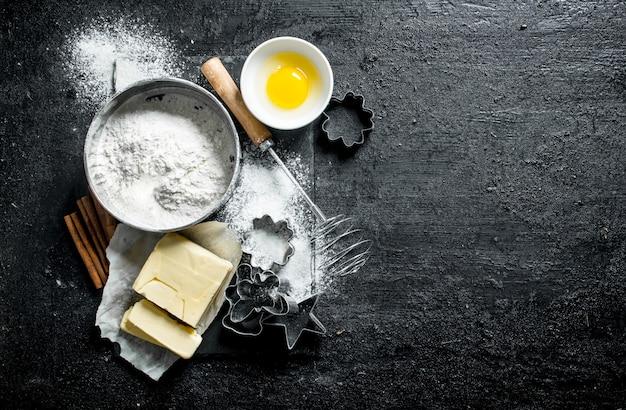 Просейте муку и формы для выпечки печенья. на черной деревенской поверхности