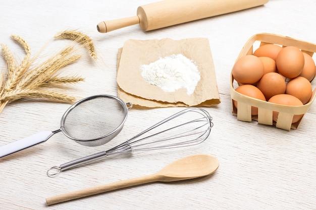 Сито, венчик и скалка. бумага, мука, яйца в плетеной коробке и колоски пшеницы. белый фон. вид сверху
