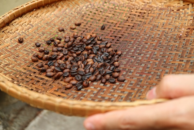 Sieving dark roasted coffee beans with threshing basket for making coffee at home