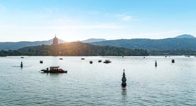 Sightseeing boats and stone pagodas and distant pagodas in west lake scenic area, hangzhou, china