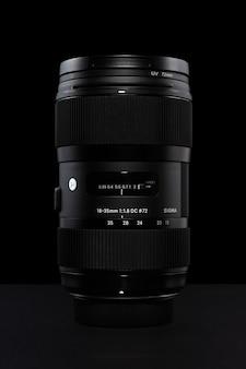 Объектив sigma 18-35 мм f1.8 dc hsm art для nikon, вертикально стоящий на черном фоне.