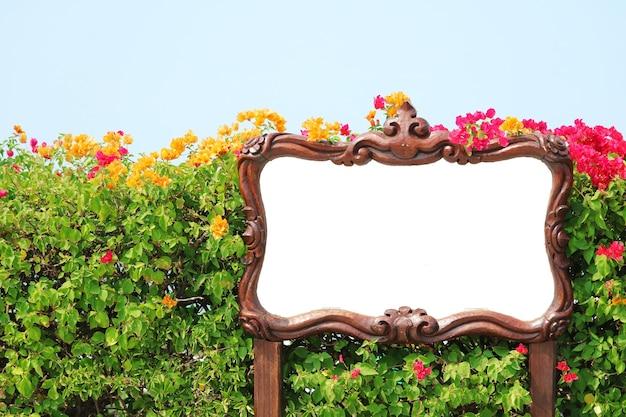 サインと白い背景は、フラワーガーデンに配置された木製のフレームで作られています