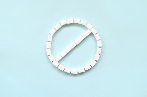 Sign of the ban of sugar cubes on a pastel blue background