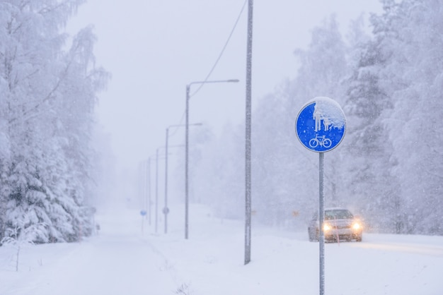 Sign of a bike path and a pedestrian on the road in winter