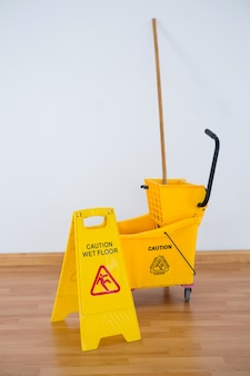 Sign board with mop bucket against wall
