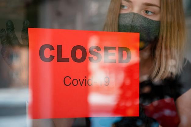 레스토랑의 새로운 정상 폐쇄로 정문 문에 닫힌 covid 19 잠금에 서명합니다. 보호용 의료 마스크 장갑을 낀 여성이 텅 빈 카페 창문에 닫힌 표지판을 걸고 있습니다. 중소기업 위기.
