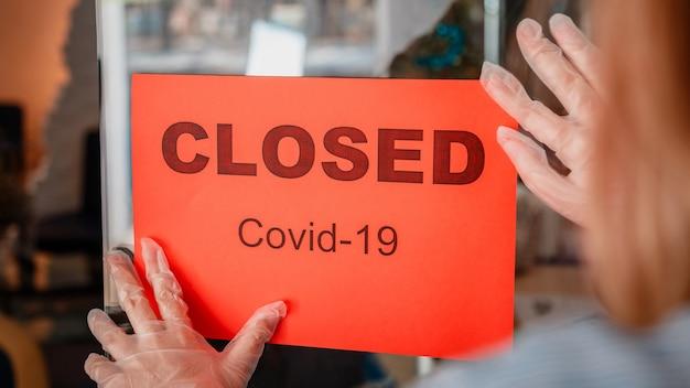 보호 의료 분야에서 새로운 정상 폐쇄 여성으로 상점 입구 문에 폐쇄된 covid 잠금 서명...