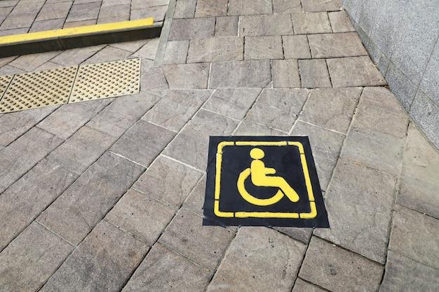 コンクリート通りのタイルの障害者用スロープを示す標識