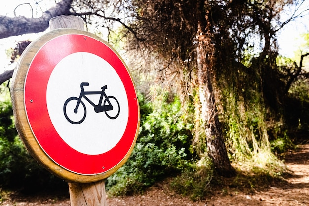 Sign forbidden to ride a bicycle, placed in a forest.