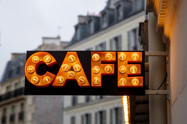 The sign from light bulbs with the word cafe on town street.