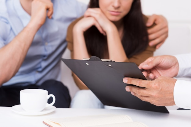 Подпишите здесь. крупный план вдумчивой молодой пары, сидящей на диване, в то время как мужчина в строгой одежде указывает на буфер обмена с документом