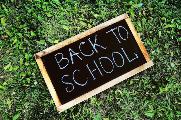 Подпишите в форме доски со словами обратно в школу мелом крупным планом на фоне ...