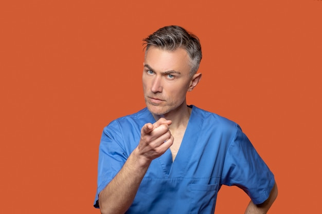 Sign language. serious young adult man in blue suit pointing with finger at camera on orange background