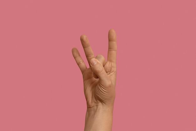 Sign language symbol isolated on pink