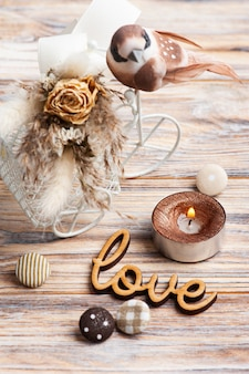 Sign love, bouquet of dry flowers on decorative bike with litle brown bird and lit candle on the table. greeting card for wedding or holiday in natural tones