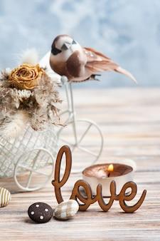사랑, 저 작은 갈색 새와 테이블에 조명 된 촛불 장식 자전거에 마른 꽃의 꽃다발에 서명합니다. 자연스러운 색조의 결혼식이나 휴가를위한 인사말 카드
