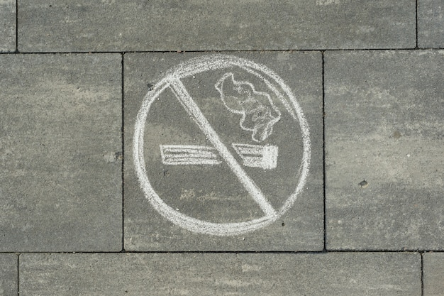 Sign no smoking painted on the grey sidewalk