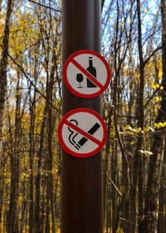 Знак не пить, не курить на столбе в парке перед деревьями
