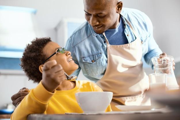 愛情の印。陽気な若い父親が息子を抱き締め、グラスに牛乳を注いで彼とおしゃべり