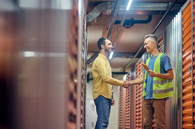 Знак согласия. двое дружелюбных радостных мужчин, обменивающихся рукопожатием, стоят в профиль возле складских гаражей в освещенной современной комнате