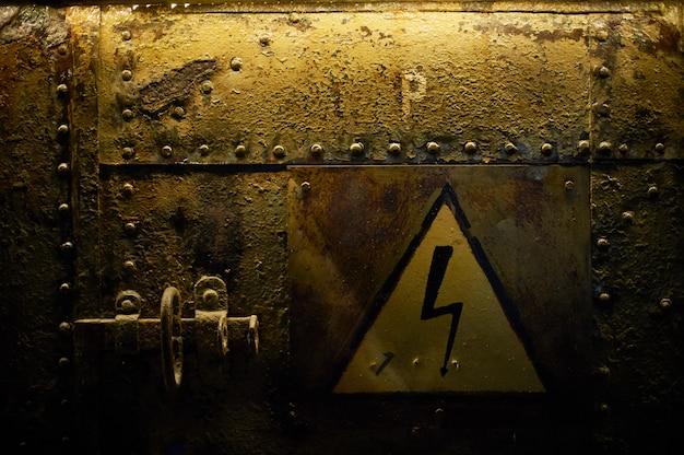 Знак высокого напряжения, приклеенный на ржавый металлический фон с заклепками.