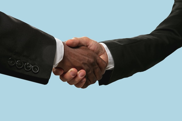 미래에 대한 공동 계획의 표시. 팀워크 및 커뮤니케이션. 두 남자 손을 떨고 블루 스튜디오 배경에 고립. 도움, 파트너십, 우정, 관계, 비즈니스, 공생의 개념.