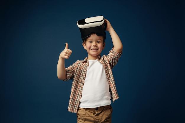 Okのサイン。青いスタジオの背景に分離されたバーチャルリアリティヘッドセットメガネとジーンズとシャツの小さな男の子または子供。最先端技術、ビデオゲーム、イノベーションのコンセプト。