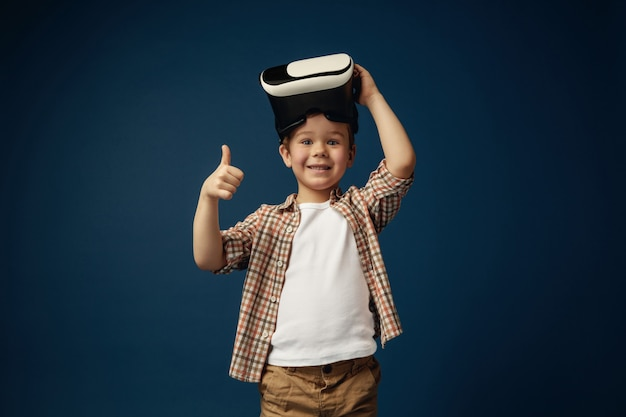 Sign of ok. little boy or child in jeans and shirt with virtual reality headset glasses isolated on blue studio background. concept of cutting edge technology, video games, innovation.