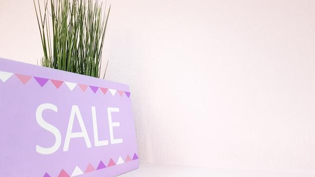 婦人服店の緑の植物と淡いピンクの壁の背景に碑文割引で棚にサインします。銘板の販売。ショッピングセンターのブティックでの割引。