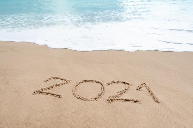 Знак на песчаном пляже с мягкой волной белой пены