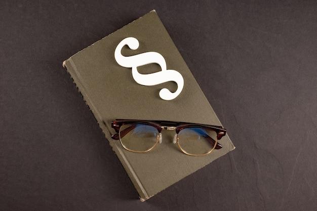 Знак абзаца очки и книги на черном фоне камня