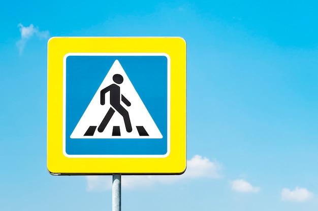 Знак пешеходного перехода с желтой рамкой на фоне голубого неба в солнечный день. копировать пространство