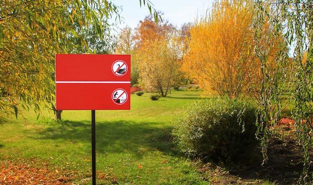 Знак, запрещающий кормить птиц и бросать камни в водоем парка. макет бесплатный.