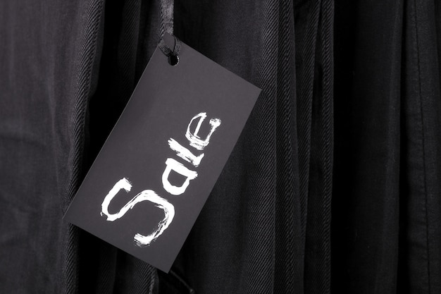 Sign sale on black pants and jeans background.