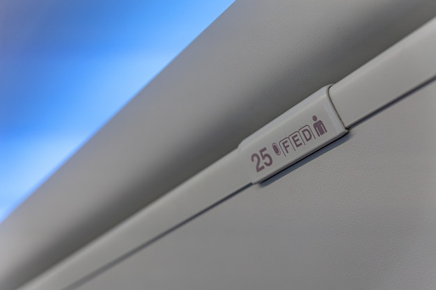Sign of seat number with number and letter on luggage shell inside passenger airplane