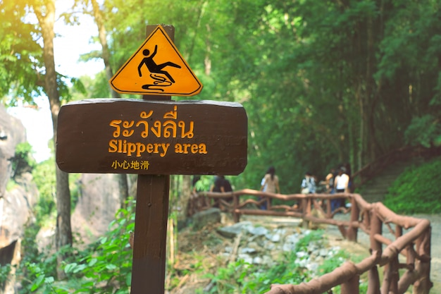 Sign showing a slippery area, thai and chinese alphabet mean beware slippery.