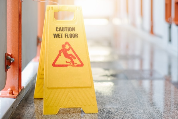 Sign showing warning of caution wet floor at airport.
