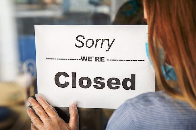 Знак извините, мы закрыты на входной двери магазина в связи с новым нормальным закрытием женщина в защитных перчатках медицинской маски вешает закрытый знак на входной двери кафе. блокировка коронавируса covid 19 для местного бизнеса.