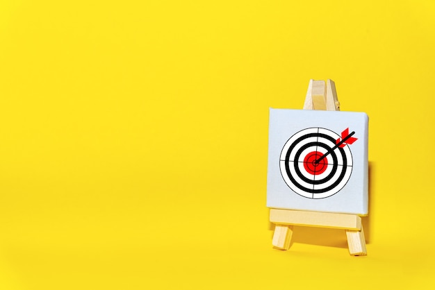 Sign stand with an arrow in the target  on a yellow background hit exactly on center. tactics of advertising targeting.