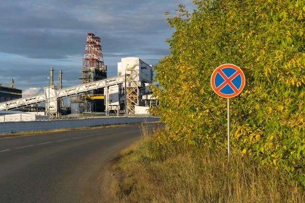 산업 경관이 있는 도로를 배경으로 표지판 정지 및 주차 금지