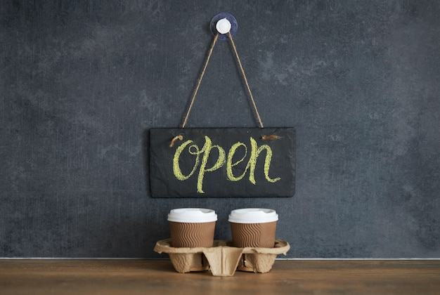 A sign that says open on cafe, on a black chalk board. after quarantine. takeaway coffee glasses on dark space. business opening